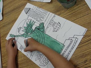Coloring in statue of liberty on paper.